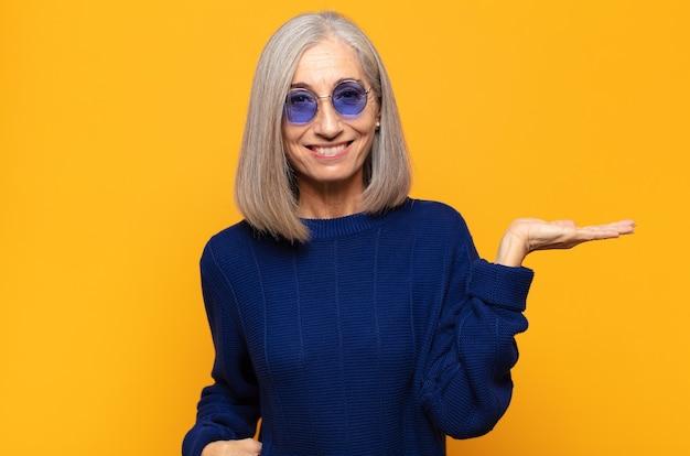 Mulher de meia-idade sorrindo, sentindo-se confiante, bem-sucedida e feliz, mostrando o conceito ou ideia no espaço da cópia ao lado