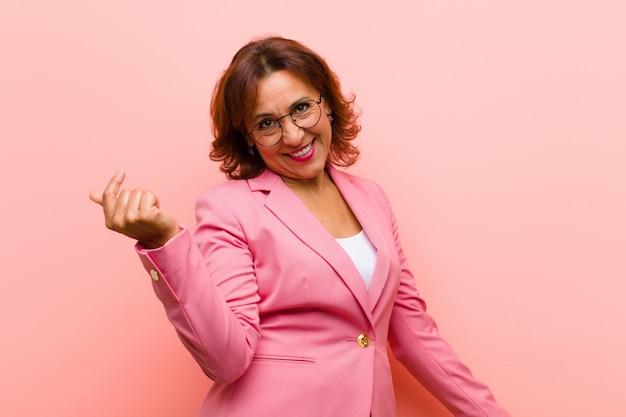 Mulher de meia idade sorrindo, sentindo-se despreocupada, relaxada e feliz, dançando e ouvindo música, se divertindo em uma festa contra a parede rosa