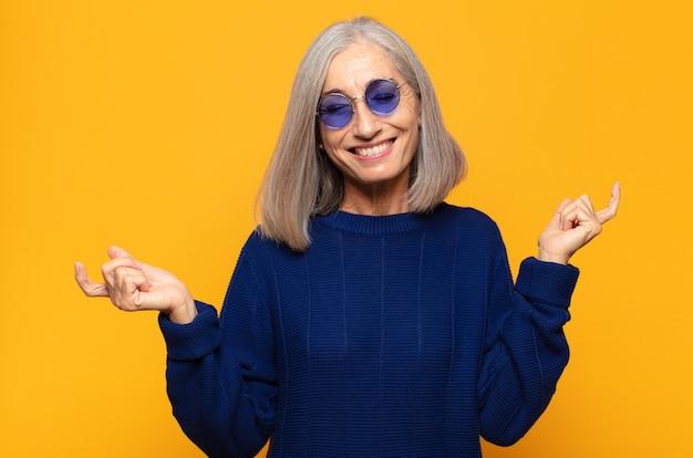 Mulher de meia idade sorrindo, sentindo-se despreocupada, relaxada e feliz, dançando e ouvindo música, se divertindo em uma festa