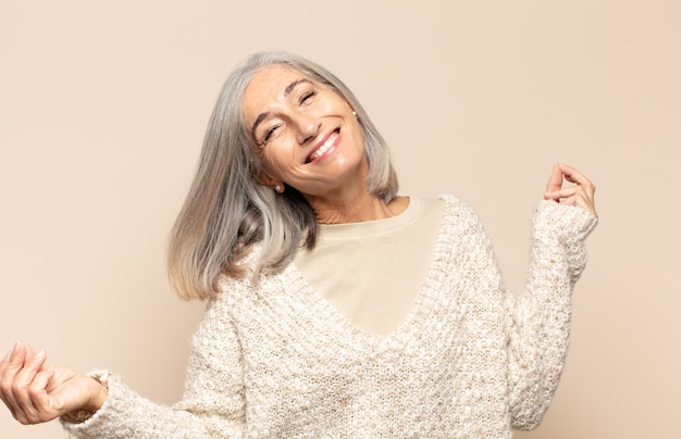 Mulher de meia-idade sorrindo, sentindo-se despreocupada, relaxada e feliz, dançando e ouvindo música, se divertindo em uma festa