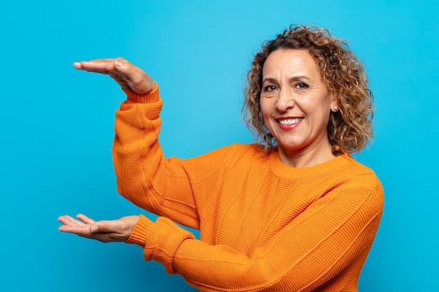 Mulher de meia-idade sorrindo, sentindo-se feliz, positiva e satisfeita, segurando ou mostrando um objeto ou conceito no espaço da cópia