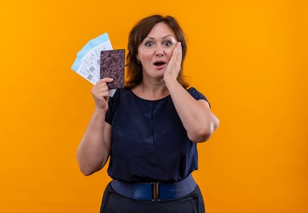 Mulher de meia-idade surpreendida com bilhetes e carteira com a mão na bochecha