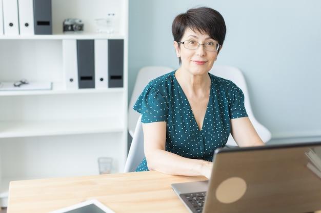 Mulher de meia-idade trabalha no escritório e usa um laptop