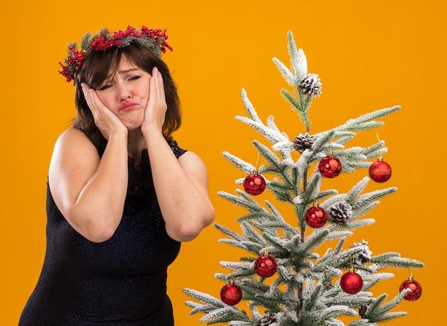 Mulher de meia-idade triste com coroa de flores de natal e guirlanda de ouropel em volta do pescoço em pé perto da árvore de natal decorada, mantendo as mãos no rosto isoladas em uma parede laranja