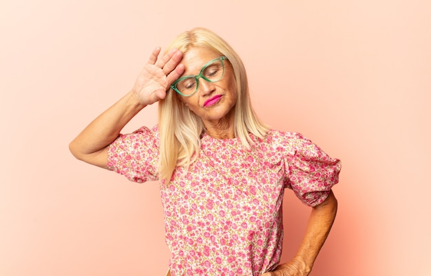Mulher de meia-idade triste, frustrada, nervosa e deprimida, cobrindo o rosto com as duas mãos, chorando