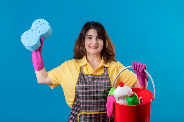 Mulher de meia-idade usando avental e luvas de borracha segurando um balde com ferramentas de limpeza e uma esponja