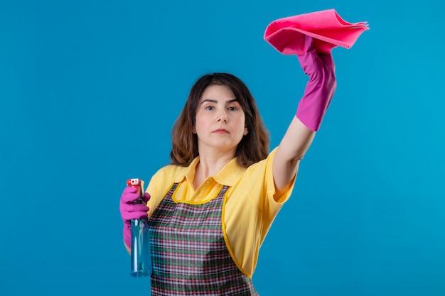 Mulher de meia-idade usando avental e luvas de borracha segurando um spray de limpeza e tapete com expressão séria