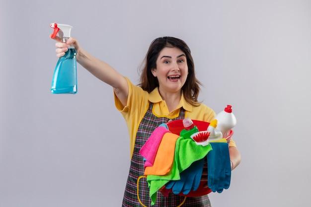 Mulher de meia-idade usando avental segurando balde com ferramentas de limpeza e spray de limpeza sorrindo alegremente saiu e feliz em pé sobre a parede branca
