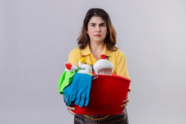 Mulher de meia-idade usando avental segurando um balde com ferramentas de limpeza e parecendo descontente com o rosto carrancudo em pé sobre uma parede branca