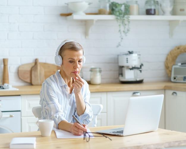 Mulher de meia-idade usando fones de ouvido, fazendo anotações enquanto estudava online na cozinha