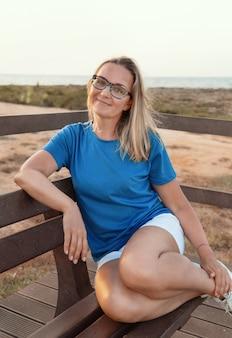 Mulher de meia idade usando óculos e camiseta azul e sentada com as pernas dobradas em um banco de madeira ao pôr do sol. maquete de camiseta