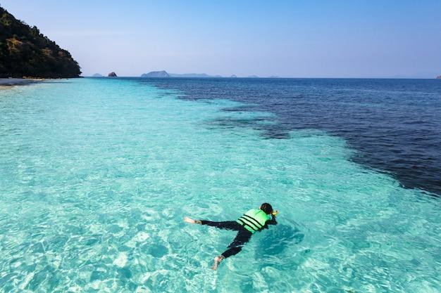 Mulher de mergulho em águas cristalinas, mar de andaman
