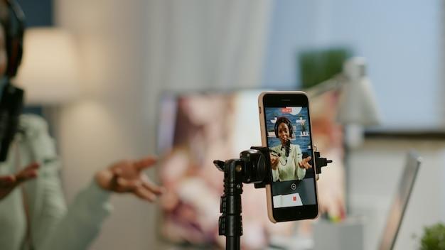 Mulher de mídia social falando no microfone profissional durante a gravação de podcast para o canal do youtube no smartphone. show on-line criativo produção no ar, host de transmissão pela internet streaming de vídeo ao vivo