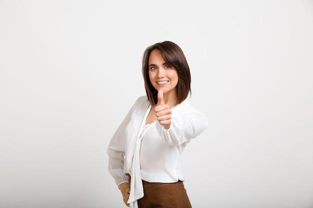 Mulher de moda bem sucedida satisfeito polegares para cima