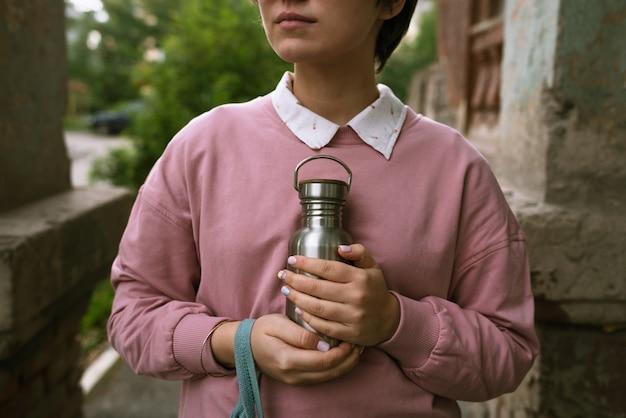 Mulher de moletom rosa segurando uma garrafa ecológica de metal sustentável nas mãos ao ar livre