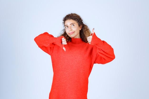 Mulher de moletom vermelho, mostrando sinais de subida e descida do polegar.
