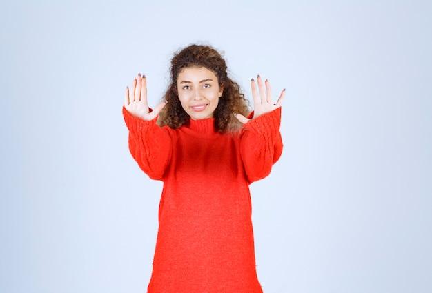 Mulher de moletom vermelho, parando alguma coisa.