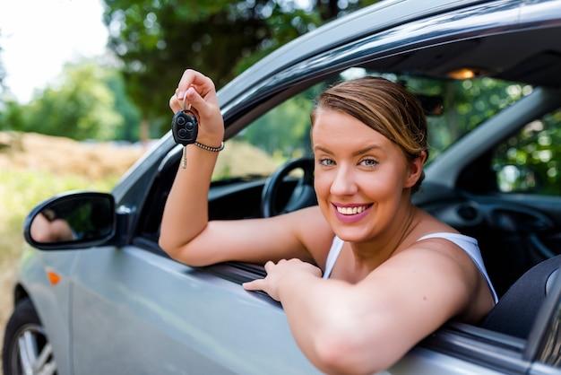 Mulher de motorista de carro sorrindo mostrando novas chaves do carro e carro