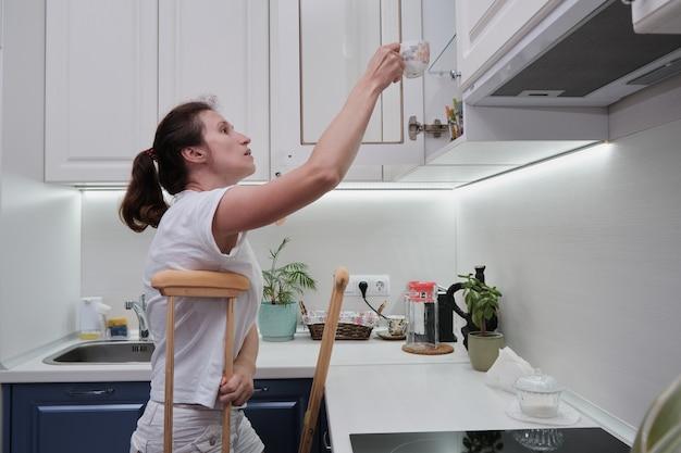Mulher de muletas lava a louça na cozinha