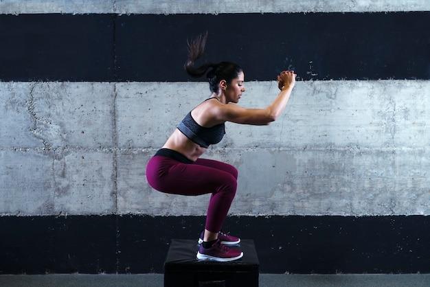 Mulher de musculação forte e fitness em roupas esportivas, fazendo treinamento de salto no ginásio