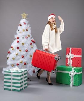 Mulher de natal com chapéu de papai noel segurando sua bolsa de viagem e dizendo tchau