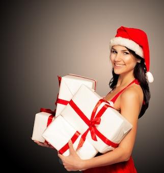 Mulher de natal de chapéu de papai noel segurando presentes de natal sorrindo feliz e animado. linda linda multirracial caucasiana asiática santa menina isolada no fundo preto.