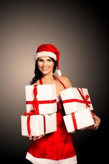 Mulher de natal de chapéu de papai noel segurando presentes de natal sorrindo feliz e animado. linda linda multirracial