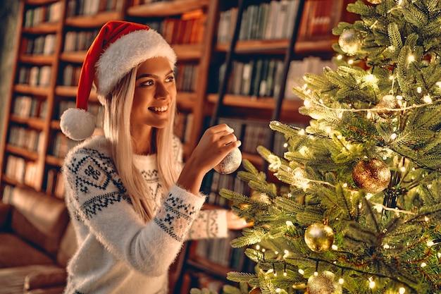 Mulher de natal. feliz natal e boas festas. menina feliz decorar a árvore de natal dentro de casa - bokeh mágico de natal. na manhã antes do natal. rapariga loira apaixonada por retrato de perto
