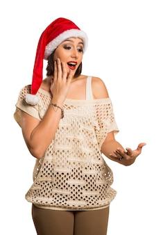 Mulher de natal mostrando a palma da mão vazia com espaço de cópia sorrir surpreendentemente em pé. bela jovem sorridente com chapéu de papai noel vermelho mostrando copyspace.