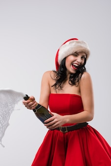 Mulher de natal que abre garrafa de champanhe
