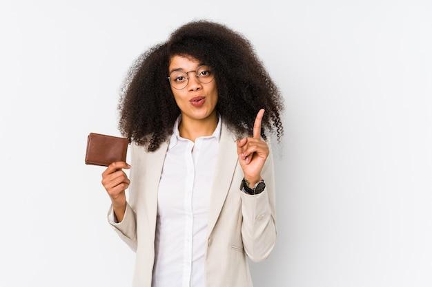 Mulher de negócio afro nova que mantem um carro do crédito isolado mulher de negócio afro nova que mantem um crédito que carhaving alguma grande ideia, conceito da faculdade criadora.