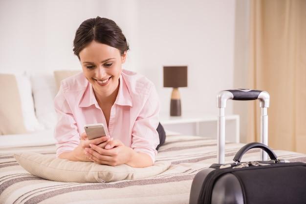 Mulher de negócio alegre que guarda o telefone e que encontra-se na cama.