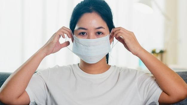 Mulher de negócio asiática deprimida que veste a máscara protetora que senta-se no sofá na sala de visitas na casa quando o distanciamento social fica em casa e o tempo de quarentena do auto, pandemia na porcelana, conceito do coronavirus.