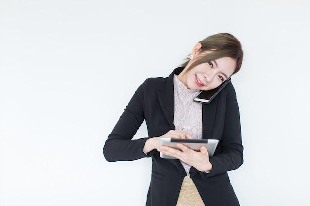 Mulher de negócio asiática nova de sorriso com tecnologia da tabuleta e telefone esperto