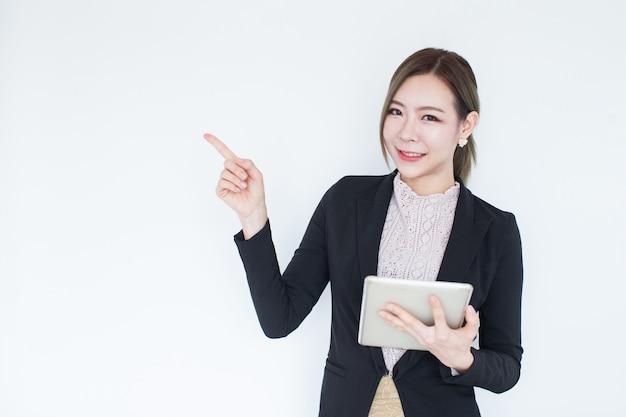 Mulher de negócio asiática nova de sorriso com tecnologia da tabuleta