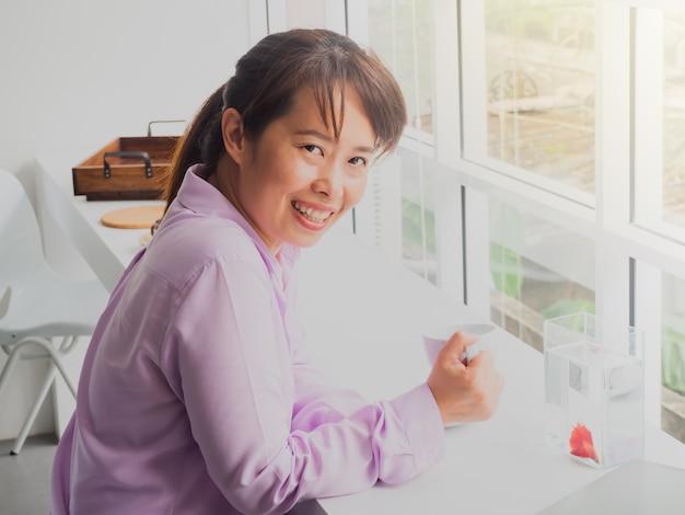 Mulher de negócio asiática que guarda o vidro do café no café com caso de mostra dos peixes.