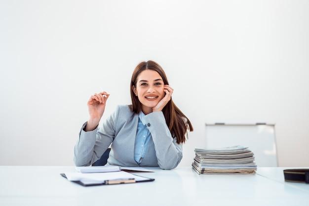 Mulher de negócio bonito no escritório brilhante com papéis.