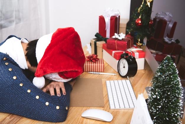 Mulher de negócio com chapéu de santa que dorme no escritório da mesa após a festa de natal e o ano novo feliz.