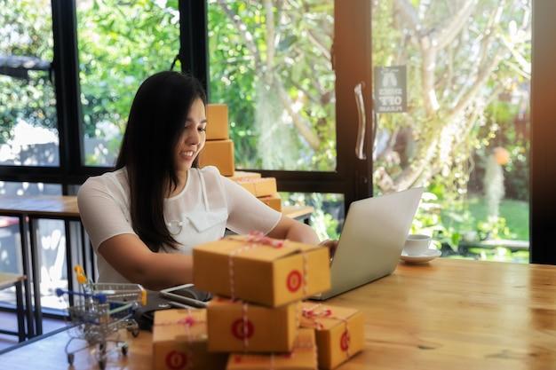Mulher de negócio com vendas em linha e envio do pacote em seu escritório domiciliário.