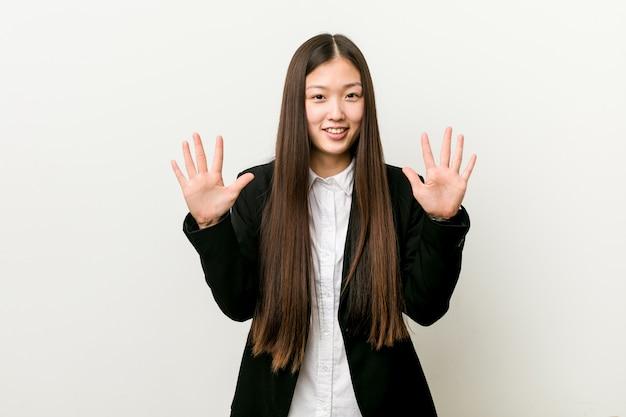 Mulher de negócio consideravelmente chinesa nova que mostra o número dez com mãos.