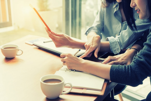 Mulher de negócio de dois asiáticos que trabalha junto com a tabuleta digital no escritório. conceito de equipe de negócios