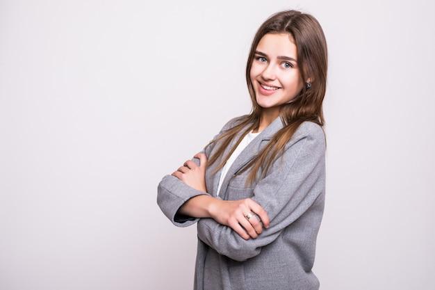 Mulher de negócio de sorriso com mãos dobradas contra o fundo branco. sorriso aberto, braços cruzados.