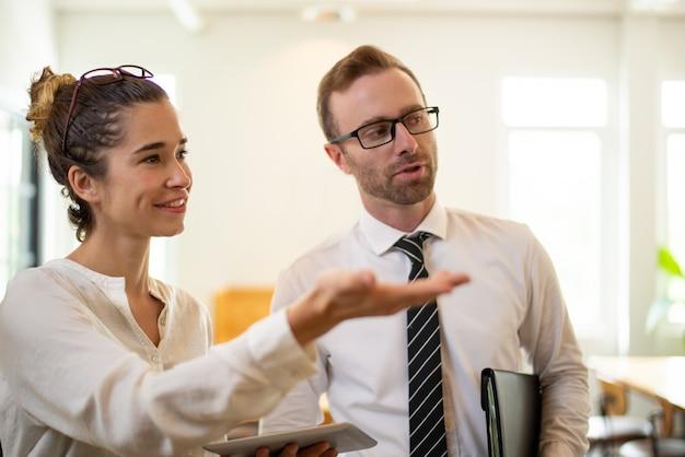 Mulher de negócio de sorriso que apresenta algo ao colega masculino.