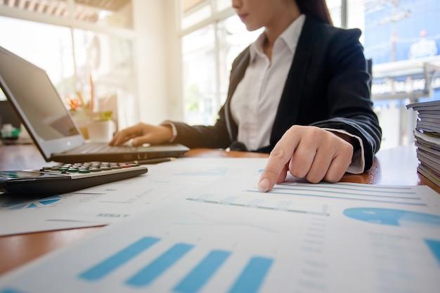 Mulher de negócio em trabalhar com relatórios financeiros e computador portátil no escritório.