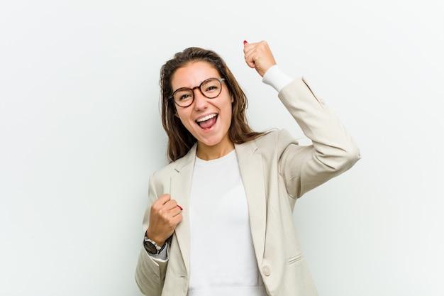Mulher de negócio europeia nova que levanta seu punho após uma vitória, conceito do vencedor.