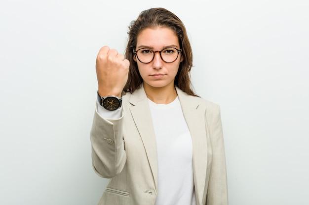 Mulher de negócio européia nova que mostra o punho à câmera, expressão facial agressiva.
