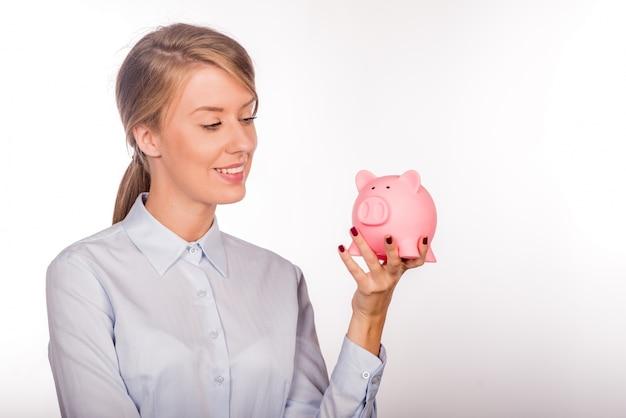 Mulher de negócio feliz com suas economias em um cofrinho