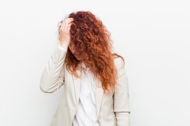 Mulher de negócio natural nova do ruivo contra o branco que esquece algo, batendo na testa com palma e fechando os olhos.