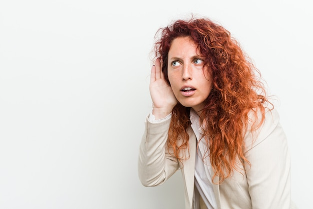 Mulher de negócio natural nova do ruivo isolada contra a parede branca que tenta escutar uma fofoca.