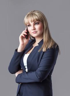 Mulher de negócio no terno que fala em um telefone de pilha.